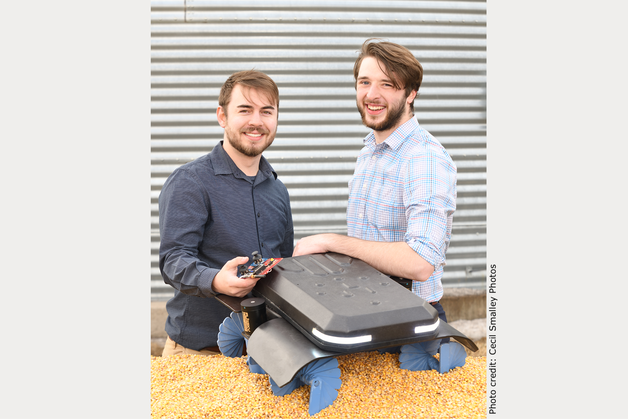 University of Nebraska Omaha undergraduate students Benjamin Johnson and Zane Zents with their Grain Weevil robot that is sitting on top of a pile of grain.
